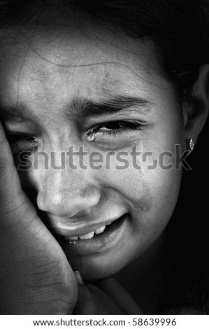 Crying girl, tears on cheeks, low light key, added grain, black and white - stock photo