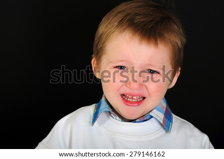 Crying little blond boy with blue eyes on a black background  - stock photo