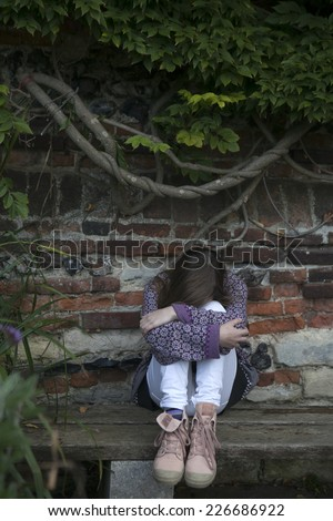 crying little girl fourteen years old sitting on the bench in the garden - stock photo