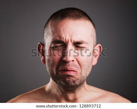 Crying man isolated on black background. - stock photo