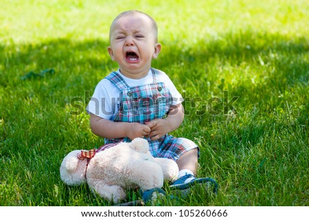 Crying toddler sitting on a grass - stock photo