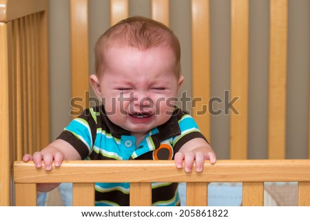 Crying unhappy baby standing in his crib - stock photo