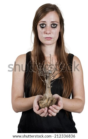 Crying woman depicting concept of dying nature holding a dead bonsai tree. Isolated on white.