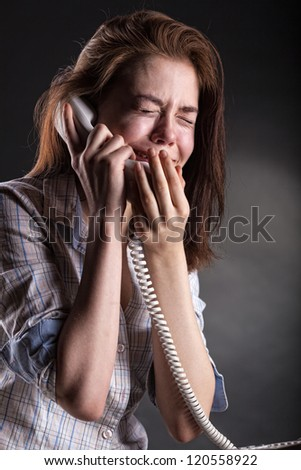Crying woman with a phone on a dark background - stock photo