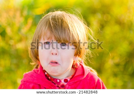 Crying 4 years girl looking away outdoors - stock photo