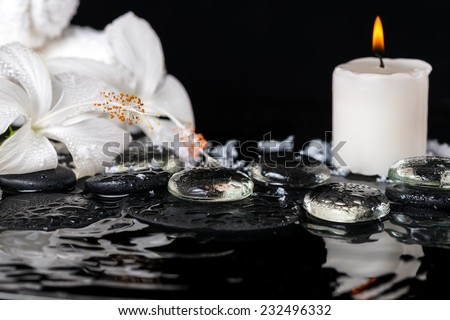 cryogenic spa concept of delicate white hibiscus, zen stones with drops, snow, ice, candles and towels on ripple water - stock photo
