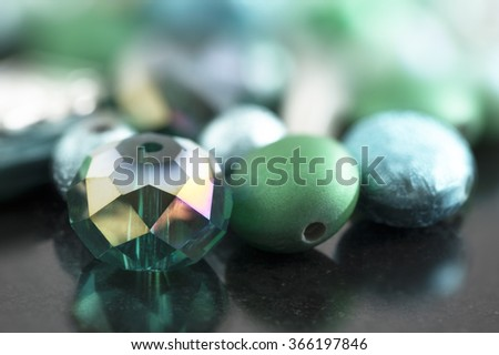 Crystal and glass coated beads with green and teal hues, on dark surface. - stock photo