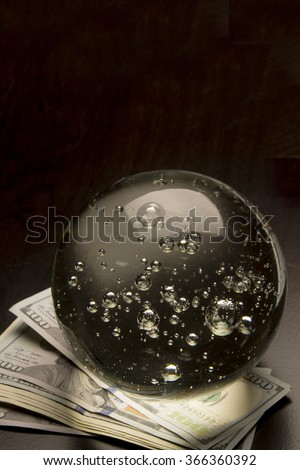 Crystal ball and money/Economy Prediction/Crystal ball sits on a pile of money - stock photo
