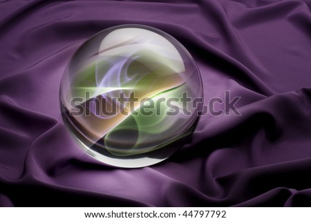 Crystal ball with colorful smoky interior shot on purple satin background - stock photo