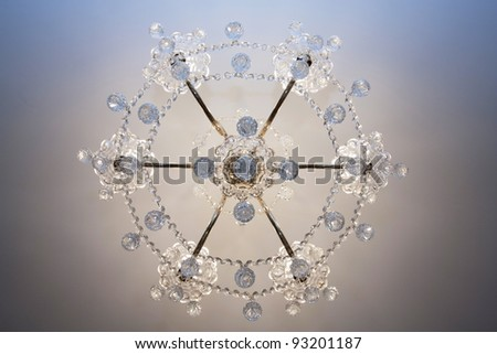 Crystal chandelier with the included bulbs against a wall