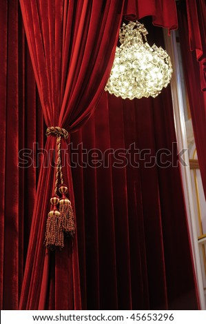 Crystal chandelier with theater stage red curtains - stock photo