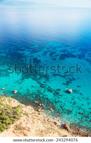 Crystal clear blue sea with small rocks