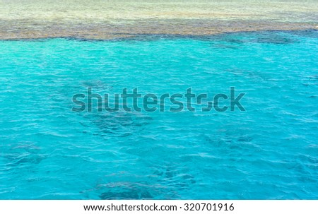 Crystal clear turquoise blue sea water lapping gently against a sandy shore or sand bank, conceptual of an idyllic summer vacation in the tropics - stock photo