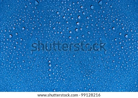 Crystal clear water drops over blue background.