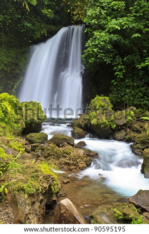 Crystal clear water tumbles down a tropical waterfall in Arenal National Park in Costa RIca - stock photo
