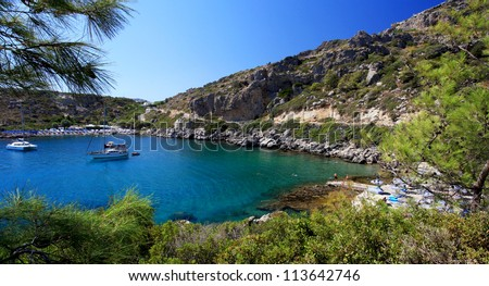 Crystal clear waters at in a torquois hidden bay in Rhodes Greece - stock photo