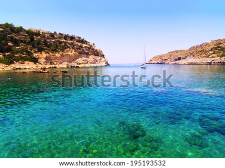 Crystal clear waters in a turquoise bay in Rhodes - stock photo