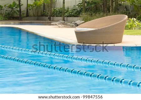 Crystal cline swimming pool with round cozy chair on the side - stock photo
