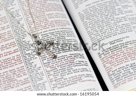 Crystal Cross on Bible Page - stock photo