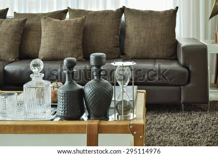 Crystal drink set and sandglass on glass top table with wooden frame and dark brown sofa set in the living room - stock photo