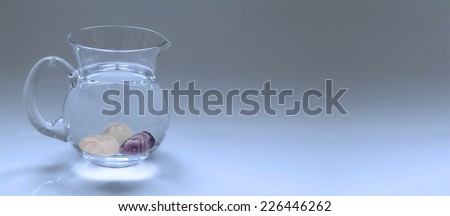 Crystal Gem Essence Water in Jug  -  Graduated blue banner background with a clear glass jug of water containing tumbled gem stones resting at the bottom of the jug intended for making a gem essence - stock photo