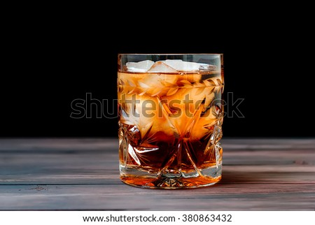 crystal glass of whiskey with ice on a wooden table on a dark background - stock photo