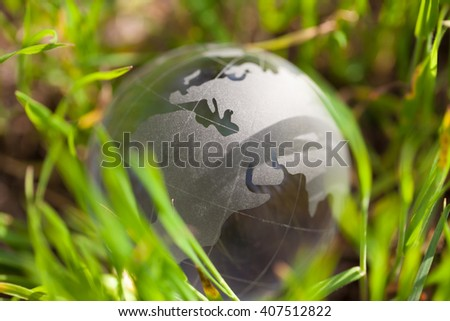 Crystal glass sphere globe lying in green grass. Concept for environment, ecology and green world. Macro, no models, focus on North Africa and Eastern Europe - stock photo