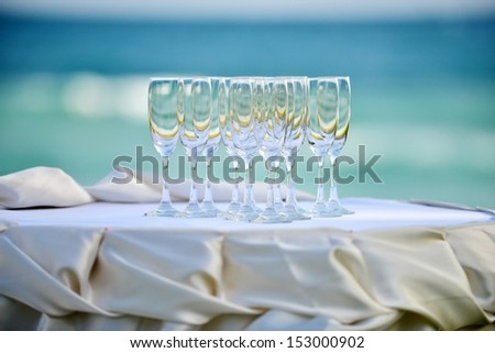 crystal glasses of champagne on the wedding Reception table  with the sea background - stock photo