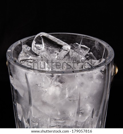 Crystal ice bucket with ice over black background