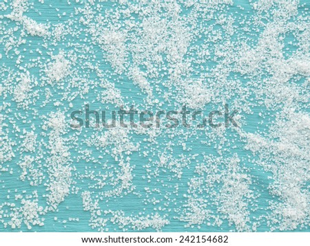 Crystal sea salt with turquoise fabric background - stock photo