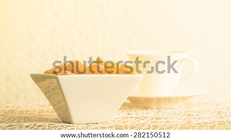 Crystallized ginger root  in white porcelain bowl and cup of tea on the background. Shallow DOF. Close-up photo, horizontal, warm tone - stock photo
