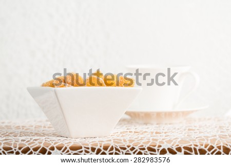 Crystallized ginger root  in white porcelain bowl and cup of tea on the background. Shallow DOF, horizontal - stock photo