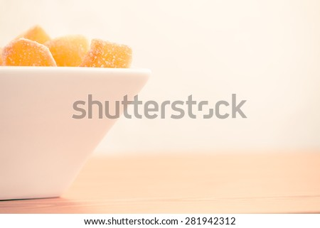 Crystallized ginger root  in white porcelain bowl. Bowl is cut vertically. Shallow DOF. Close-up photo, warm tone, horizontal - stock photo