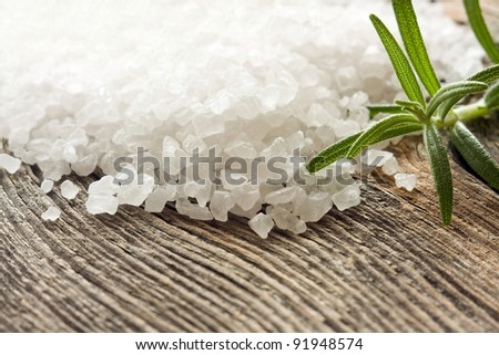 Crystals of sea salt on wooden background - stock photo