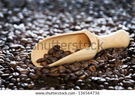 CThe coffee beans and a wooden spoon.ffee beans on wooden spoon. - stock photo