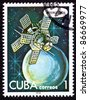 CUBA - CIRCA 1978:  A stamp printed in Cuba shows an Intercosmos satellite orbiting a planet in space.  Style of illustration is similar to futuristic space drawings from the 1950s, circa 1978. - stock photo