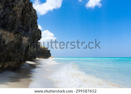 Cuba coastline with beach under blue sky - stock photo