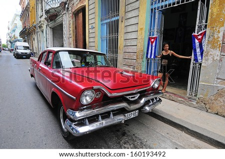 CUBA, HAVANA - JUNE 26, 2013: Girl standing near classic old American car. Classic cars are still in use in Cuba and old timers have become an iconic view and a worldwide known attraction - stock photo