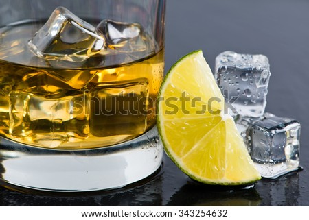 Cuba libre rum cocktail with ice cubes and lime wedge - stock photo