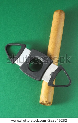 Cuban Brown Havan Cigar and Cutter on a Colored Background - stock photo