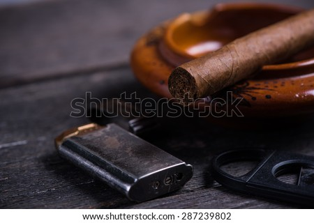 Cuban cigar in ashtray with lighter and cutter on rustic table - stock photo