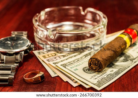 Cuban cigar with glass ashtray on a several dollar bills and gold ring with watches with on the table
