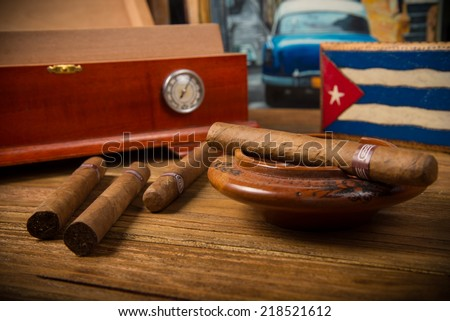 Cuban cigars and humidor with ashtray on rustic wooden table with Cuban painting of american old car in background - stock photo