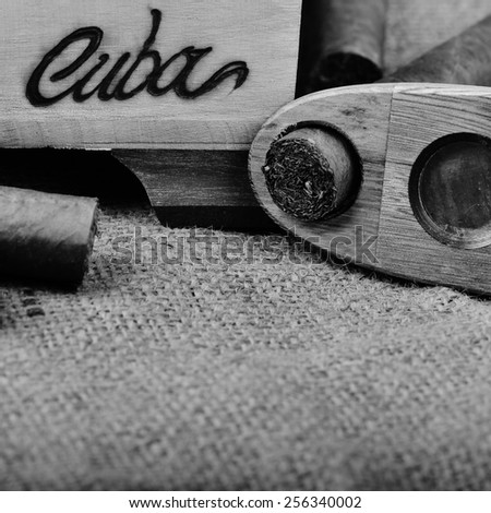 Cuban cigars with cutter on a hessian background, processed in black and white - stock photo