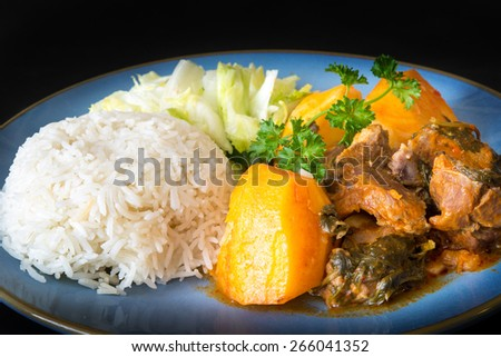 Cuban Cuisine: lamb stew in tomato sauce with potatoes,white rice and salad as side plates - stock photo