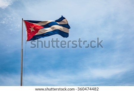 Cuban flag flying in the wind on a backdrop of blue sky. National symbol. - stock photo