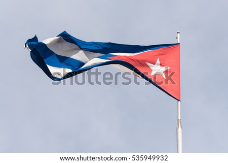Cuban flag national symbol intensely waving in a blue sky.