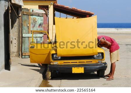 Cuban guy trying to fix his vintage american yellow car in Baracoa, Cuba - stock photo