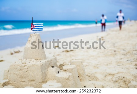Cuban Sandcastle with the country Flag on one of the most Beautiful Beach of Cuba with tourists in background - stock photo