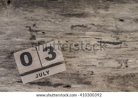 cube calendar for july on wooden surface with copy space - stock photo